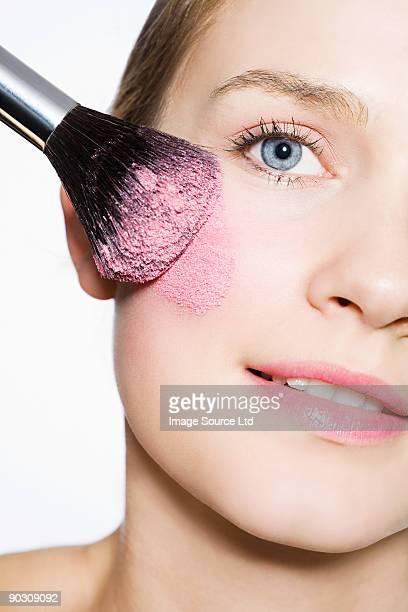 Femme avec blusher sur joue