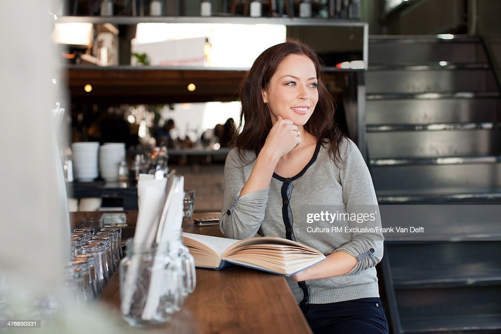 Woman with book in bar : Stock Photo