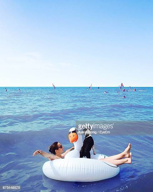 Woman With Boston Terrier Relaxing On Swan Shaped Inflatable Ring In Sea