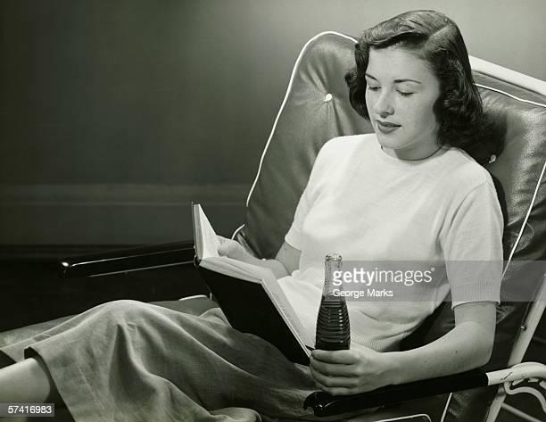Donna con bottiglia di bevande, lettura libro, (B & W
