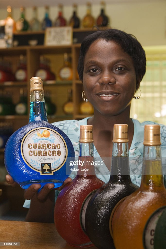 Woman with bottles of curacao, Curacao Liqueur Distillery, Landhuis Chobolobo, Salina.
