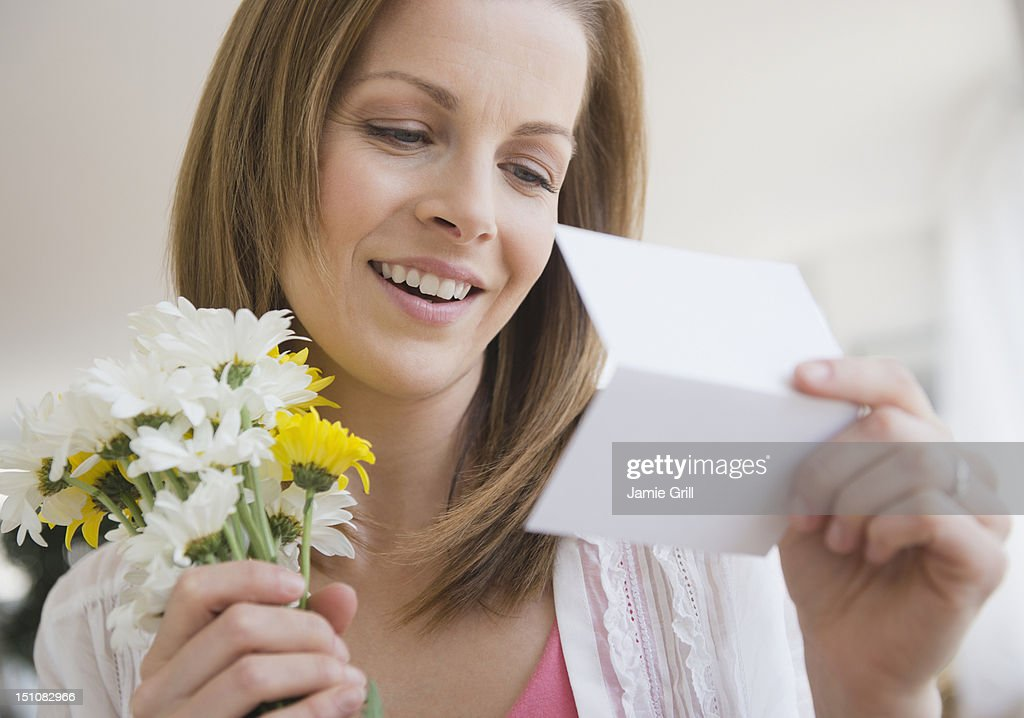 Woman with bouquet of flowers reading card : Stock Photo