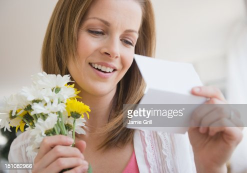 Woman with bouquet of flowers reading card : Foto stock