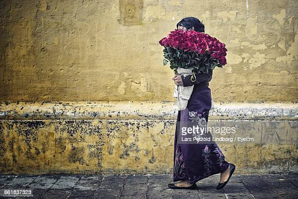 Woman With Bouquet Walking On Street