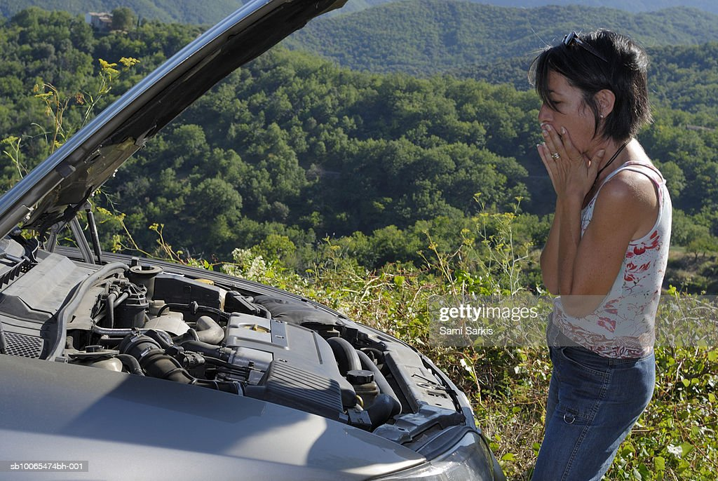 Woman with broken car in rural setting, looking at engine, side view : Stock Photo