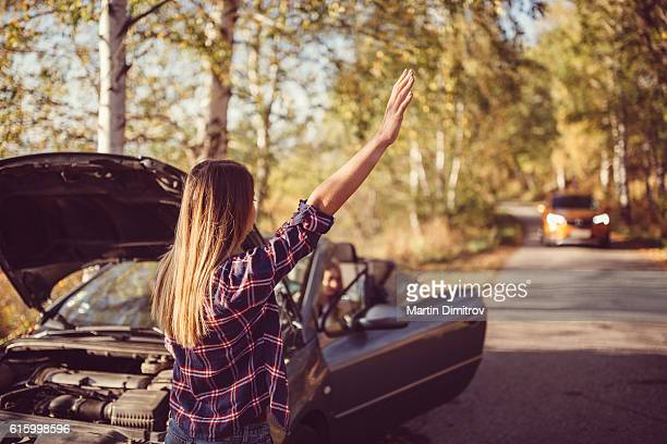 Woman with broken car on the road