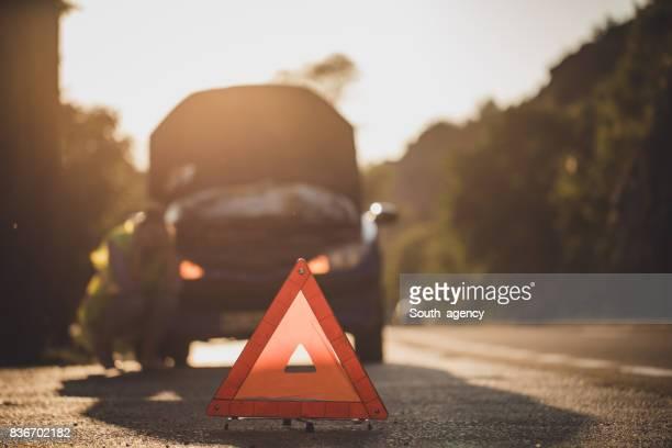 Frau mit kaputten Auto auf der Straße