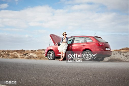 Woman with broken down car on rural road : Stock Photo