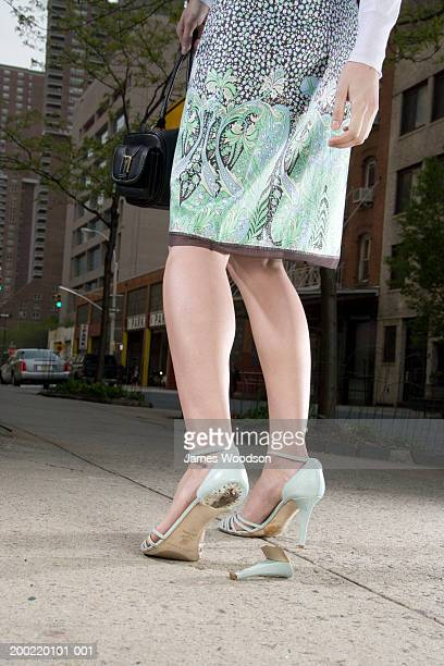 Woman with broken heel standing at roadside, low section