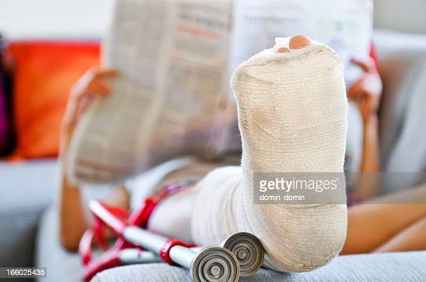 Woman with broken leg lying on sofa and reading newspaper