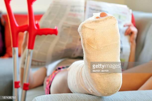 Mujer con una pierna fracturada abajo en sofá, vendaje y crutches