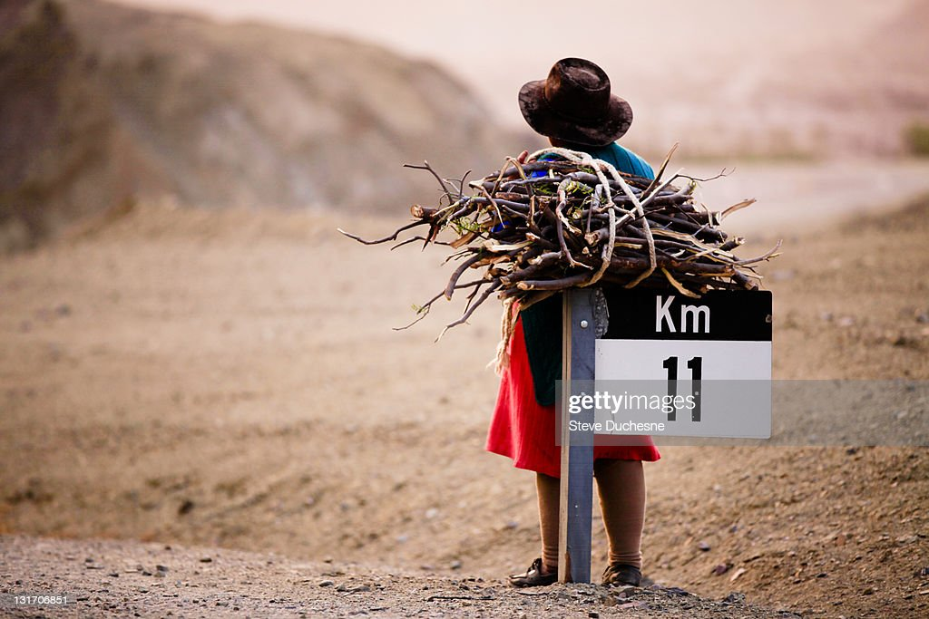 Woman with bundles of sticks standing on road