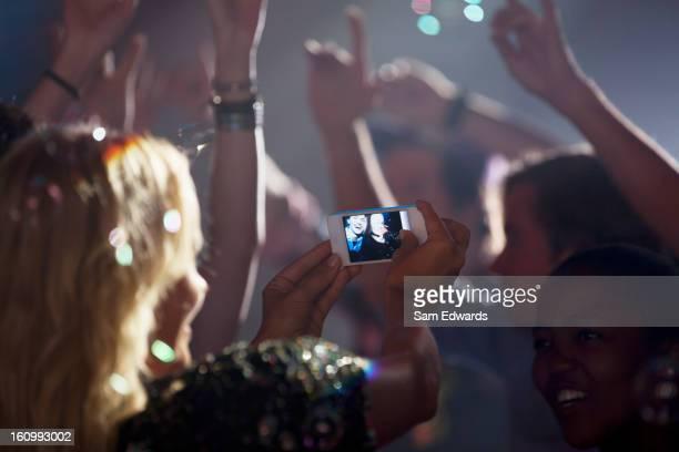 Donna con fotocamera telefono fotografare amici a ballare