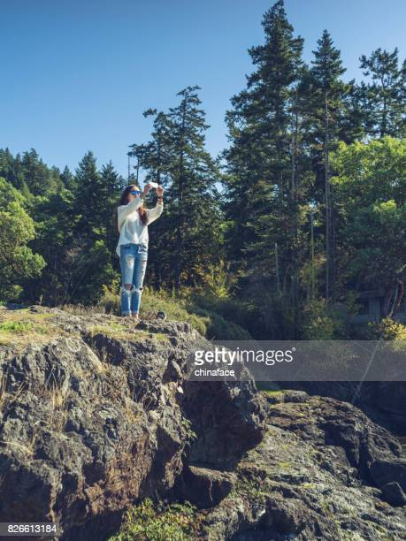 woman with camera standing on rocks against blue sea