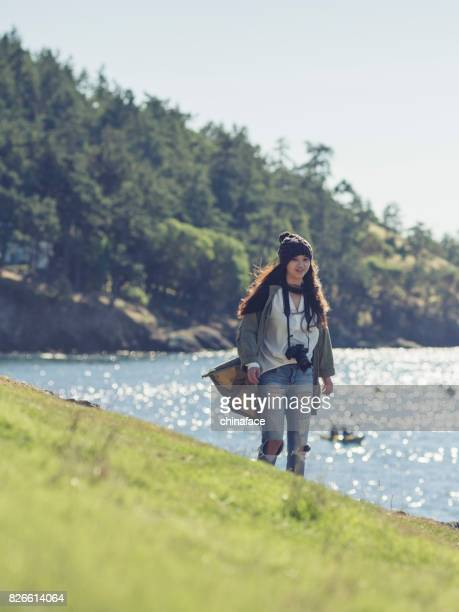 woman with camera walking along the river