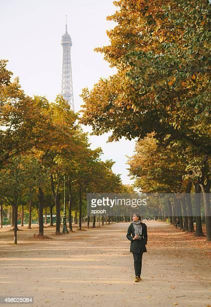 Woman with camera walking in Champ de Mars in Paris.