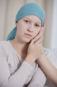 Sad woman with cancer wearing blue headscarf