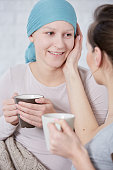 Smiling woman with cancer spending time with her friend, drinking tea and talking
