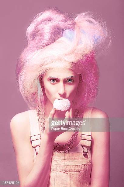 woman with candy floss hair eating cupcake