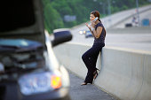 Woman with car trouble talking on cell phone