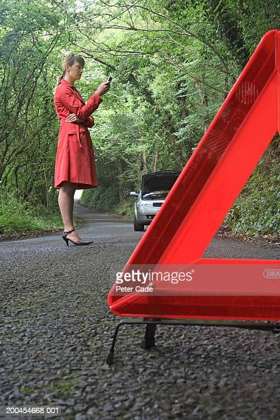 Woman with car trouble using mobile phone, warning sign in foreground