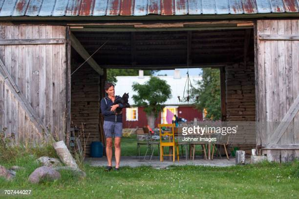 Woman with cat in front of barn