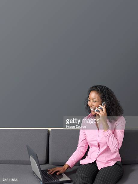 Woman with cell phone at laptop