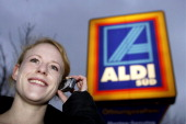 Woman with cell phone in front of Aldi logo