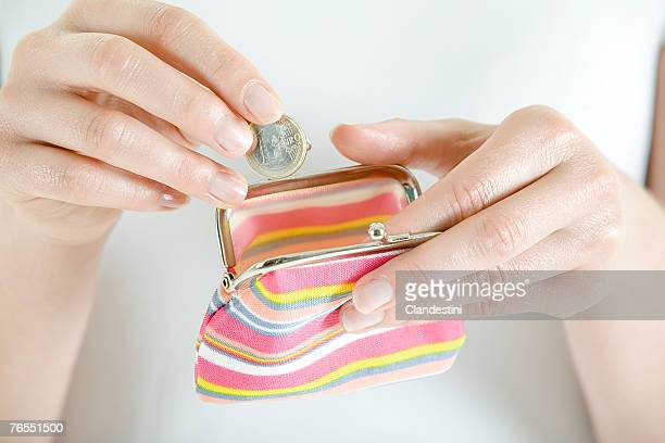Woman putting coin in change purse, close-up