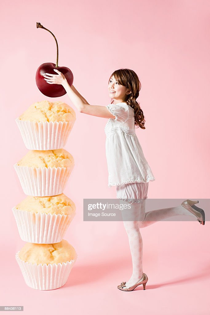 Woman with cherry and cupcakes : Stock Photo