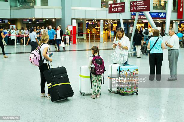 Woman with children and luggage in hall of airport Düsseldorf