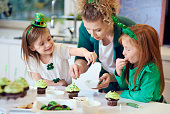Woman with children decorating cupcakes