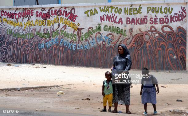 A woman with children walks past a graffiti reading ' built without book' in Conakry on April 23 2017 Conakry is hosting the 'World book capital'...