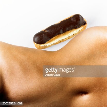 Woman with chocolate eclair 'balanced' on hip, mid section : Stock Photo