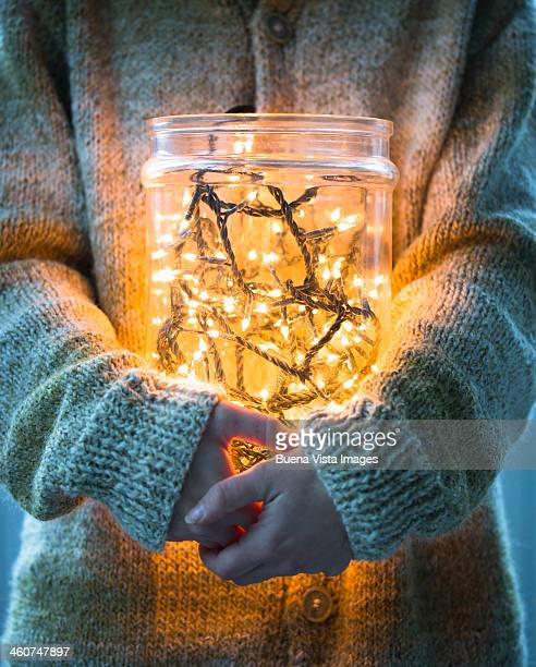 Woman with christmas lights in a jar