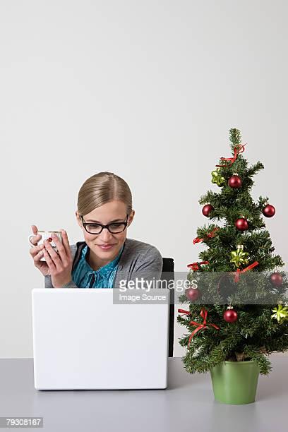 Femme avec arbre de Noël sur son bureau