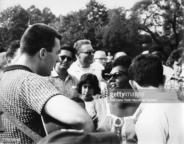 Woman with cigarette and sunglasses facing a man with eyes closed singing and playing guitar crowds surround them Washington Square Park New York New...