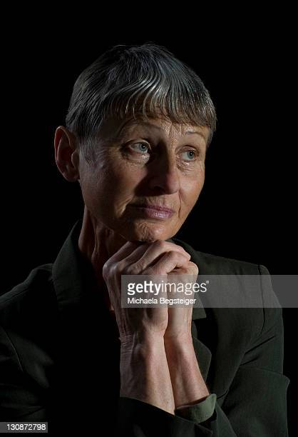 Woman with clasped hands and a hopeful glance, 60+