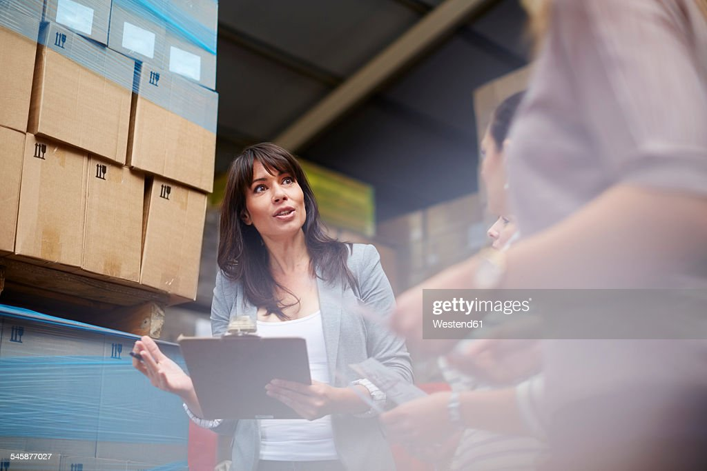 Woman with clipboard in warehouse talking to women