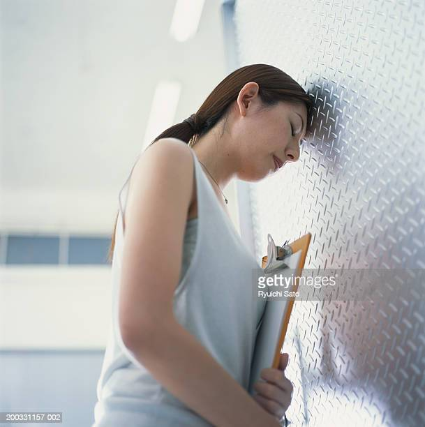 Woman with clipboard leaning head against wall, low angle view