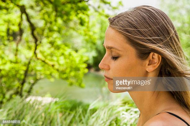 Woman with closed eyes outdoors