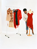 Woman with clothing rack and dress form