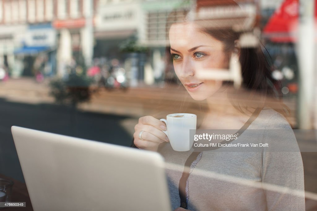 Woman with coffee and laptop looking through window : Stock Photo