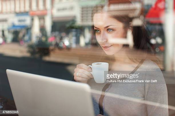 Woman with coffee and laptop looking through window