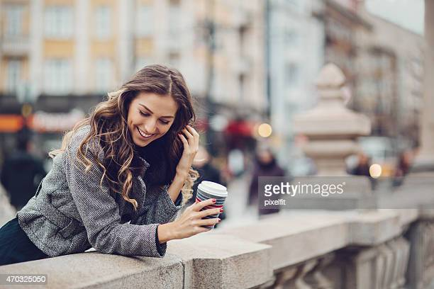 Woman with coffee cup leaning over concrete wall outside
