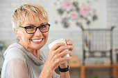 Beautiful smiling senior woman with a mug of coffee