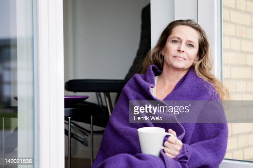 Woman with coffee in blanket outdoors