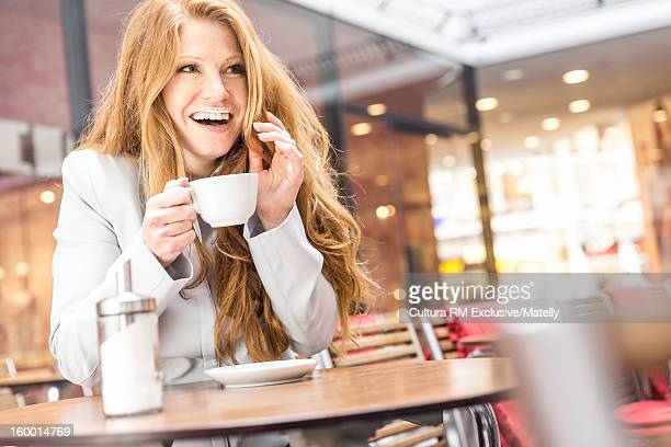 Woman with coffee mustache at cafe