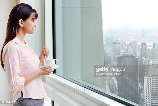 Woman with coffee staring out a window
