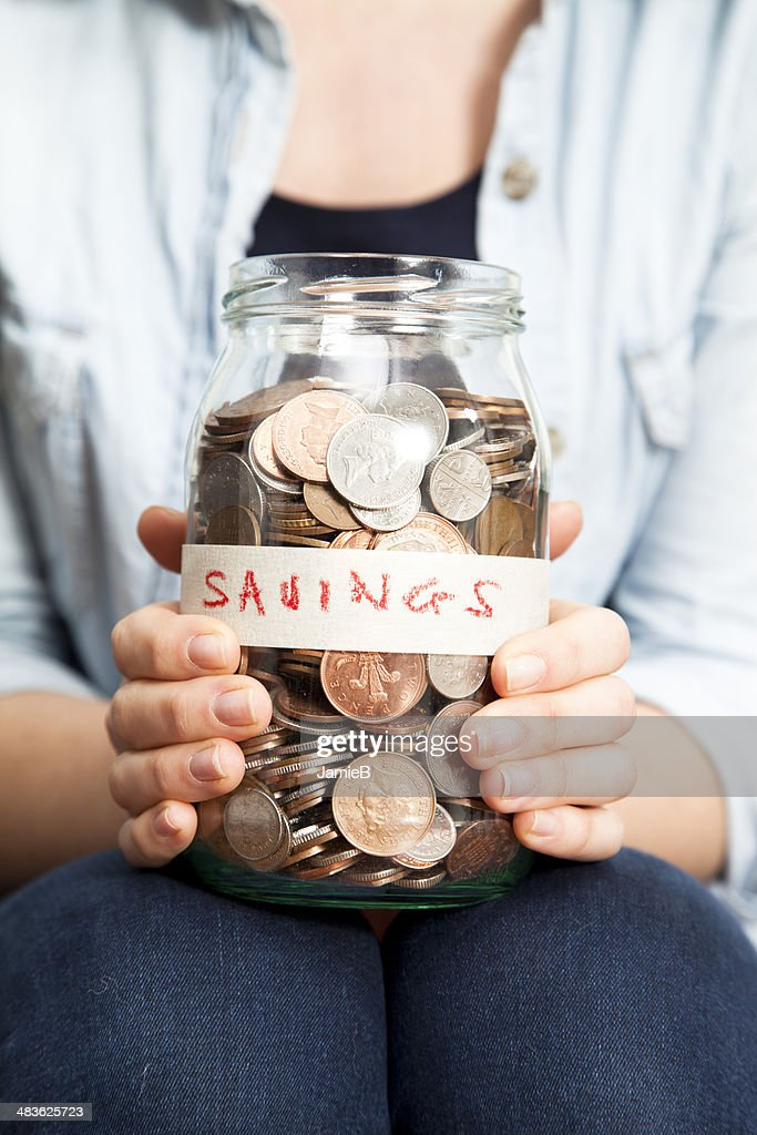 Woman with coins in jar : Stock Photo
